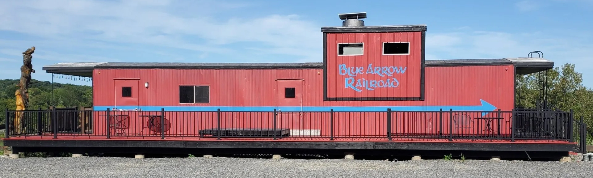 "Red train car with cafe seating and ""Blue Arrow Railroad"" painted on it"