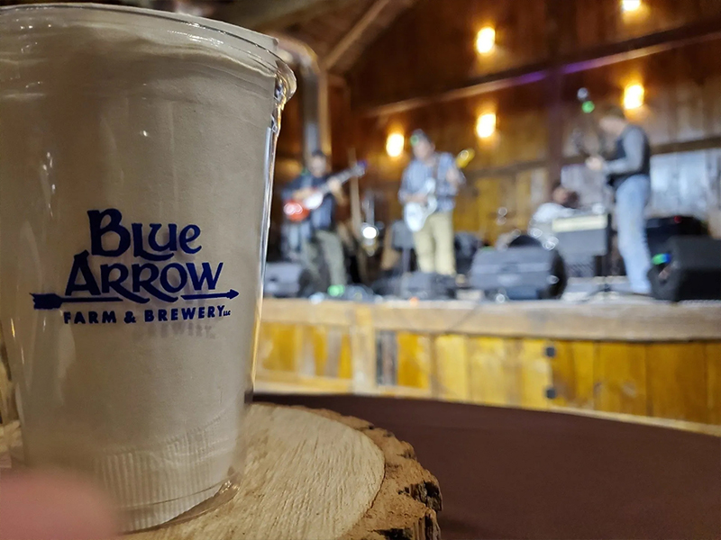 "Cup emblazoned with ""Blue Arrow Farm & Brewery,"""" with band playing in the background"